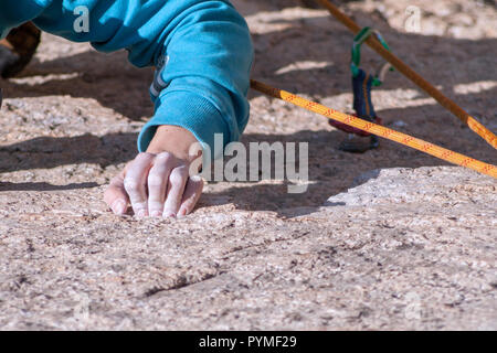 La Pedriza, Madrid, Spain. Aerial view of granite rock climber stressed hand while climbing. - Stock Photo