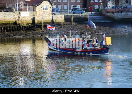 An ex-lifeboat leaves Whitby, North Yorkshire, UK harbour carrying tourists for a trip out to sea. - Stock Photo
