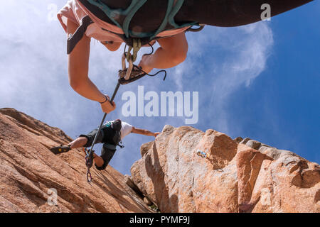 La Pedriza, Madrid, Spain. Ground view of couple climbing short technical route. Girl belaying. - Stock Photo