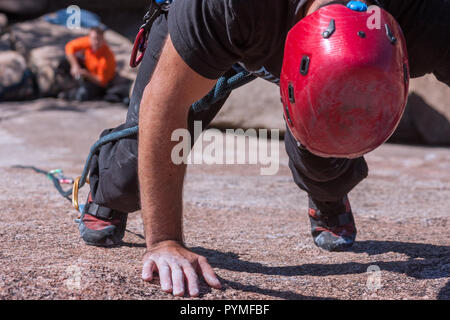 La Pedriza, Madrid, Spain. Aerial view of granite rock climber standing on his toes resting a bit before he continues. - Stock Photo