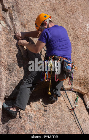La Pedriza, Madrid, Spain. Low angle view of climber dealing with a crack using layback climbing technique. - Stock Photo