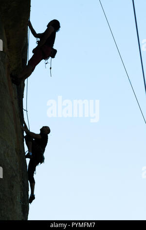 Back lit view of rock climbers climbing route at one side of the image and sky with ropes crossing the remaining image. - Stock Photo