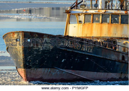 New Bedford, Massachusetts, USA - January 10, 2018: Fishing vessel Wando River plowing through thin ice in New Bedford harbor on winter afternoon - Stock Photo