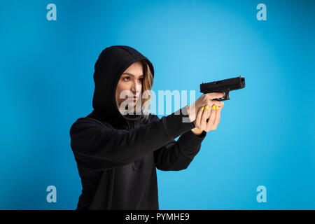 Hooded girl holding a gun pointed to the right side. Criminal face adult gangster - Stock Photo