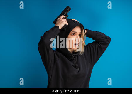 Portrait of hooded girl looking shocked while holding her hands with gun up on the head. Shot against blue background - Stock Photo