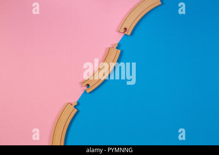 Wooden toy train rails pieces on blue and pink color background - Stock Photo