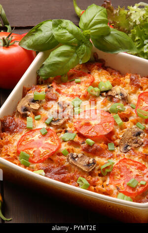 Vegetarian casserole with mushrooms and tomato in brown bowl - Stock Photo