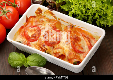 Caneloni stuffed with meat and melted cheese in white bowl over grunge wood background - Stock Photo