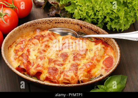 Caneloni stuffed with meat and melted cheese in brown bowl over grunge wood background - Stock Photo