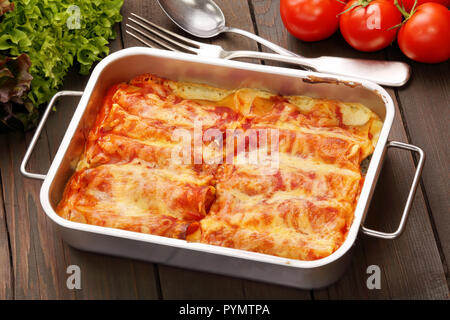 Caneloni stuffed with meat and melted cheese in metal bowl over grunge wood background - Stock Photo