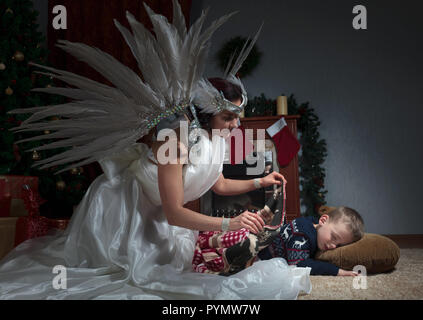 Sleeping boy under the Christmas tree and guardian angel covering him with a blanket. Angel in white dress with natural feathers. - Stock Photo