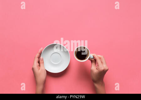 female arms hold mug of coffee on pink background. top view with cope space. - Stock Photo