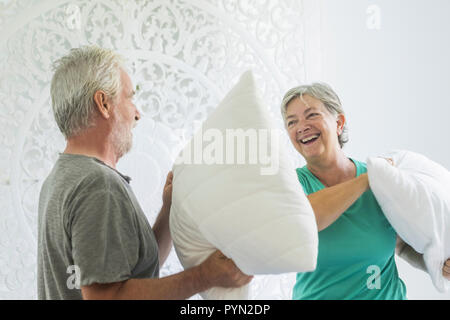 Senior couple laughing together playing battle with pillows in the bedroom. They look at each other and laugh, they spend happy moments together - Stock Photo