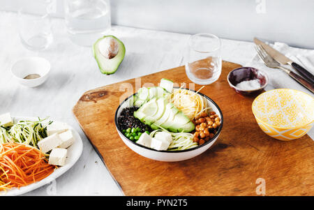 Set ingredients for cooking buddha bowl on wooden table. Quinoa, chickpea, tofu, cheese, zucchini, avocado, cucumber, spiralized vegetables - Stock Photo