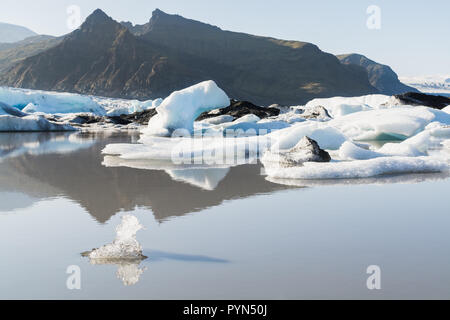 Ice floating and melting in Fjallsarlon lagoon, Iceland. Bird shaped piece of ice on the foreground. - Stock Photo