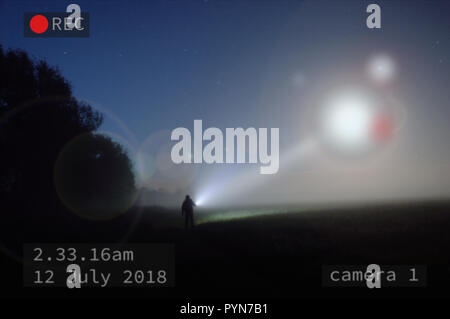 A picture at night as a UFO shines down on a silhouette of a figure standing in a misty field. With the image captured on CCTV - Stock Photo