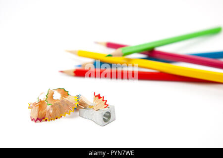 Pencil sharpener with pencil shavings on white - Stock Photo