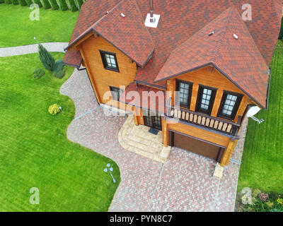 Beautiful luxury big wooden house. Timber cottage villa with with green lawn, garden and blue sky on background - Stock Photo