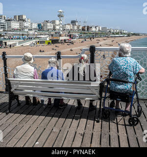elderly people sitting on brighton pier looking out across sea and sand - Stock Photo
