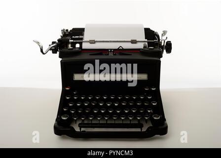 old antique typewriter with blank paper ,1930's olivetti m40/3  white/grey background,macchina da scrivere antica anni 30 - Stock Photo