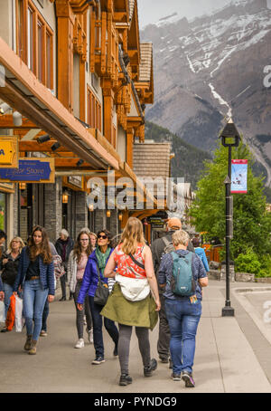 BANFF, AB, CANADA - JUNE 2018: Tourists strolling past shops in the centre of Banff. - Stock Photo