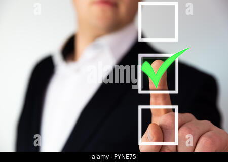 Businessman pushing checkbox button with a green tick. - Stock Photo