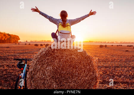 Young bicyclist sitting on haystack with raised and opened arms after a ride. Woman having rest in autumn field admiring view. Sportive lifestyle - Stock Photo