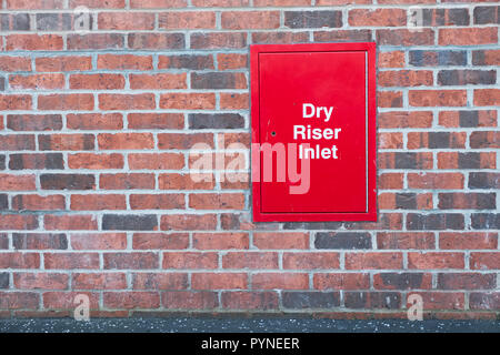 Dry riser inlet box red on brick wall for emergency fire services water connection for hose brigade engine at shopping mall retail park - Stock Photo