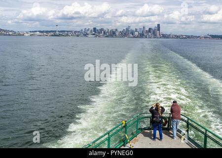 Two passengers looking at the Seattle skyline from the ferry heading to Bainbridge Island, Elliott Bay, Washington state, USA. - Stock Photo