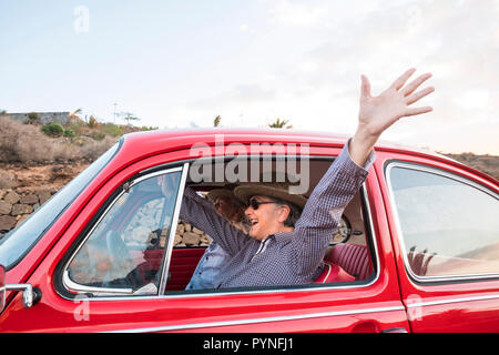 senior adult couple crazy drive with no hands in funny leisure activity. travel happy concept for retired lifestyle and couple in love. shout and laug - Stock Photo