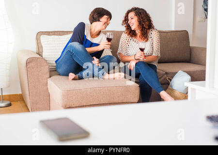 Couple of women friends sit down on the couch together enjoying the afternoon and the friendship with a cup of red wine laughing and smiling telling s - Stock Photo