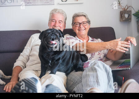 Couple of happy caucasian mature adult people man and woman sitting on the couch with a laptop and black funny pug dog over him looking at the camera  - Stock Photo