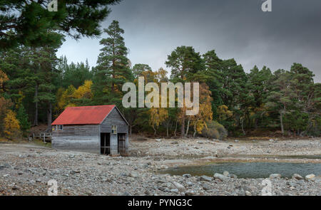 A red-roofed boathouse on the shores of Loch Vaa in the Scottish Highlands, taken during Autumn with the trees showing their bright colours. - Stock Photo