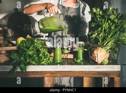 Woman pouring green smoothie from blender to bottle - Stock Photo