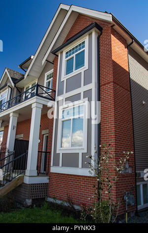 Brand new townhouse complex. Rows of townhomes side by side. External facade of a row of colorful modern urban townhouses. brand new houses just after - Stock Photo