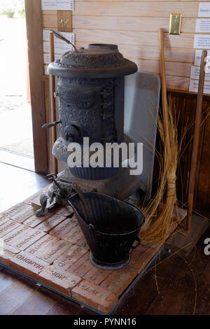 Antique Acme Oakleaf Newark Stove on brick platform with straw broom and  iron pail. Inside Wilmeth Schoolhouse, Chestnut Square, McKinney Texas. - Stock Photo
