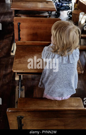 School girl in a  dress sits at vintage wooden desk in classroom. Wilmeth Schoolhouse, Chestnut Square Historical Village, McKinney Texas. portrait - Stock Photo