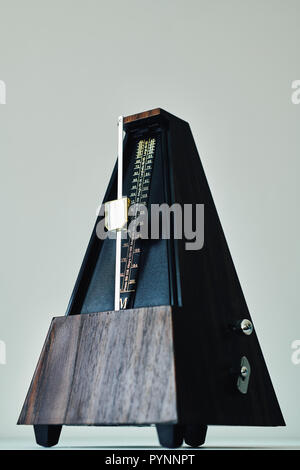 Vintage metronome, on a black background. - Stock Photo