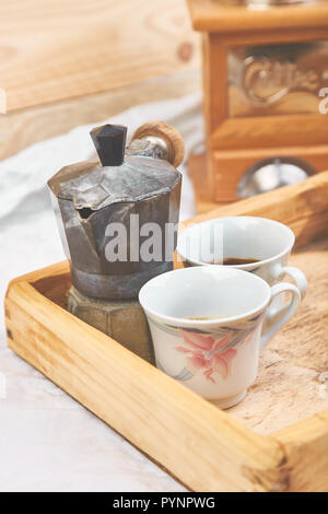 Moka coffee pot with two cup of coffe on wooden tray on white background. Old style italian coffee in soft vintage tone. Copy space. - Stock Photo