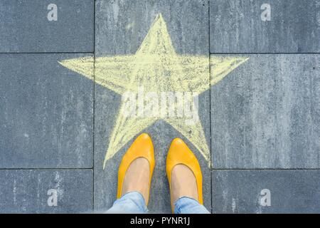 Drawing of crayons on the asphalt - star and feet of woman.