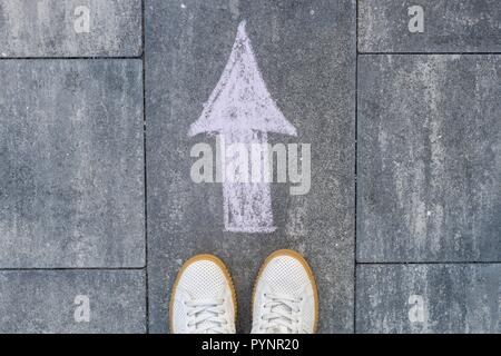 Feet and arrow on road. - Stock Photo