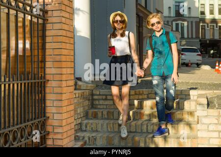 Couple of teenagers are walking through the streets of the city, holding hands. - Stock Photo