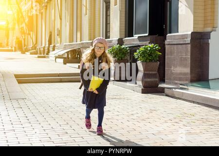 Stylish little girl with a backpack, in a coat and french beret run to school. - Stock Photo