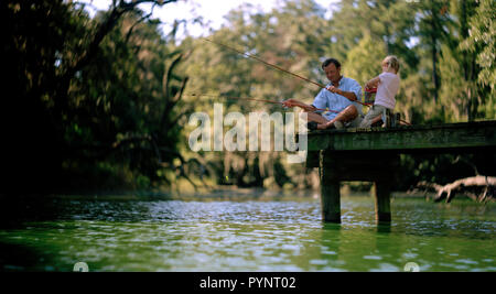 Mid-adult father fishing off a jetty with his young daughter. - Stock Photo