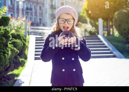 Little funny girl wearing glasses with pleasure eating a chocolate donut - Stock Photo