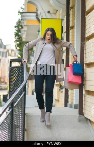 Young woman comes out of the store and slipped. - Stock Photo