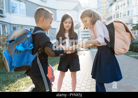 Outdoor portrait of smiling schoolchildren in elementary school. A group of kids with backpacks are having fun, talking. Education, friendship, techno - Stock Photo