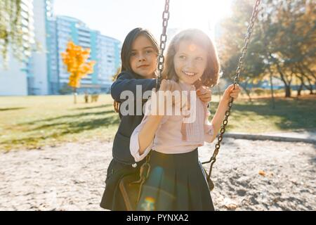 Portrait of two girls children hugging and swinging in a sunny autumn park, golden hour. - Stock Photo