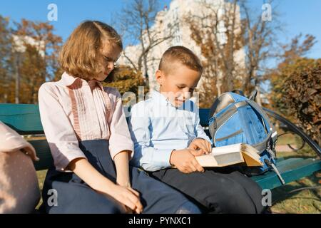 Little boy and girl schoolchildren read a book, sit on a bench, children with backpacks, bright sunny autumn day. - Stock Photo