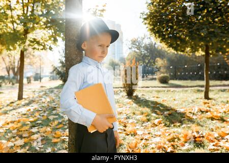 Offended little boy in hat, classic shirt holding a book in his hands. Stands near a tree in sunny autumn park, the golden hour. - Stock Photo
